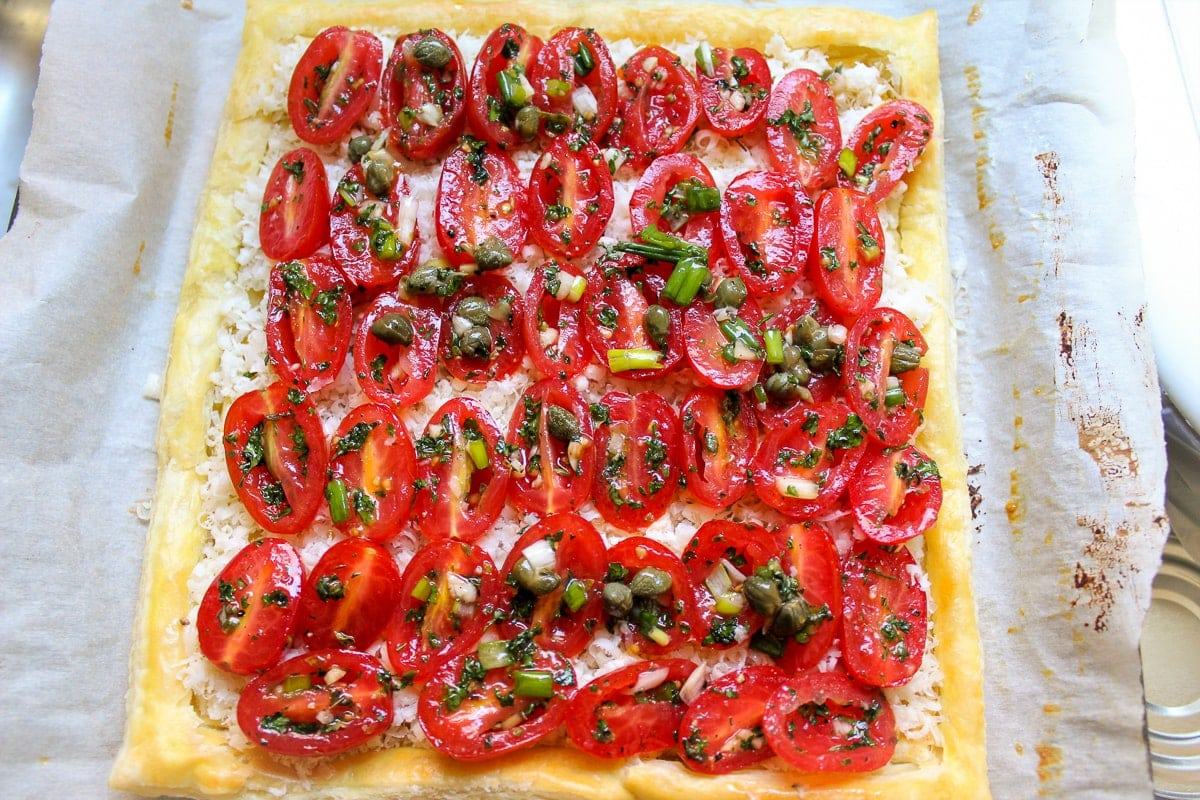 assembled tomato puff pastry tart on pan