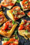 cut up tomato tart for appetizers on cutting board p4