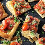 cut up Puff Pastry Tomato Tart cut into 3 inch squares on cutting board