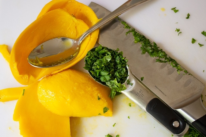 mango removed from skin and chopped cilantro on cutting board