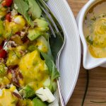 Mango Salad Dressing on salad in bowl with extra pitcher of dressing beside it p1