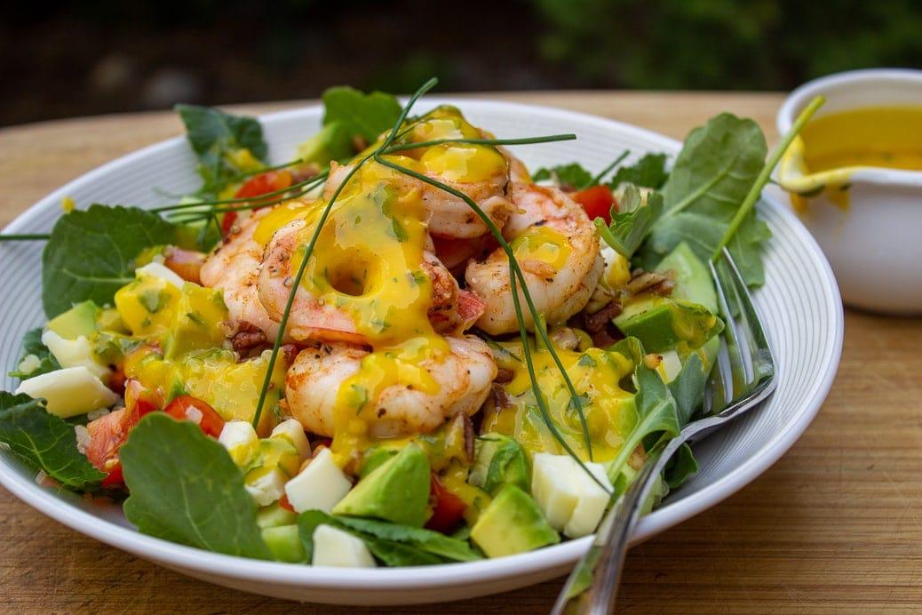 mango salad dressing on salad with shrimp in bowl