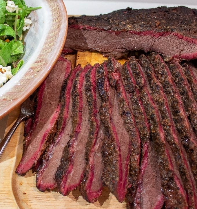 smoked brisket sliced on a cutting board served with salad
