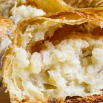 one potato knish showing flaky crust on top and mashed potatoes inside p1