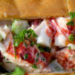 lobster roll on plate with lobster peaking out p