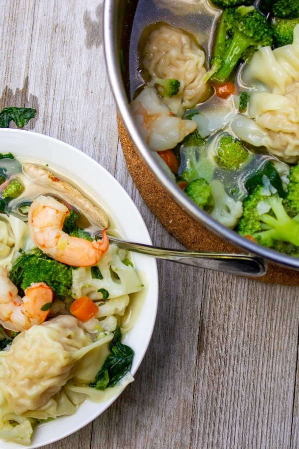 bowl of vegetable wonton soup in front of pot on wooden plank