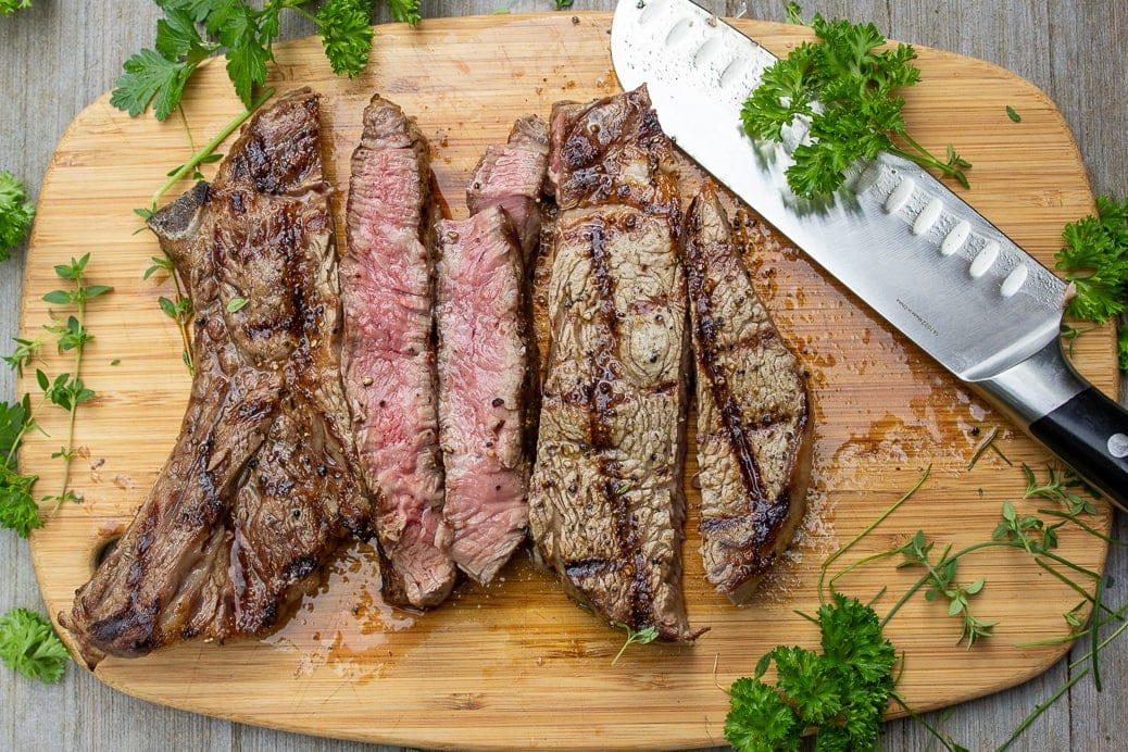 grilled steak sliced on a cutting board