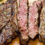 sliced grilled rib steak on cutting board p