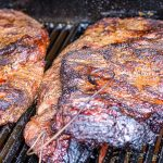 two briskets cooking in the smoker sitting on the grill p