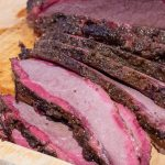 sliced smoked brisket on a cutting board showing pink smoke ring at edges p1