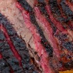 sliced smoked brisket on a cutting board showing pink smoke ring at edges. beside salad bowl p