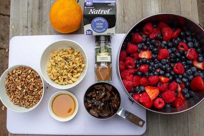 Berry Crumble ingredients - berries, pecans, walnuts, maple syrup, cinnamon, dates, whipping cream, orange
