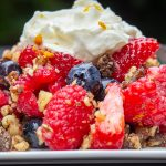 scoop of no-bake Berry Crumble on plate with whipped cream on top
