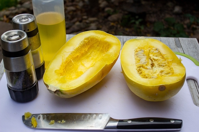 Spaghetti Squash halves, one with seeds, one scraped out. plus oil and salt