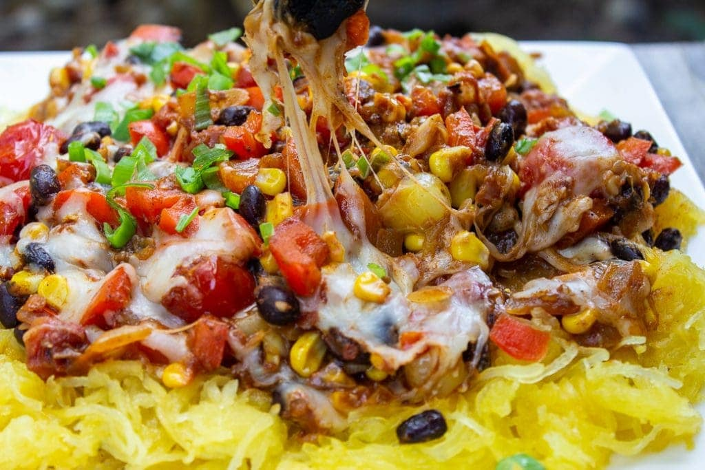 Mexican Spaghetti Squash on plate with gooey cheese pulled up with tongs