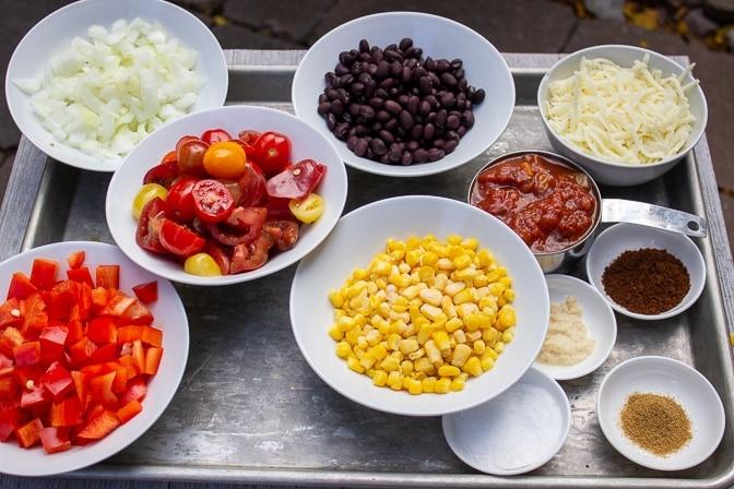 corn, beans, salsa, tomatoes, cheese, garlic, cumin, chili powder, onions, peppers