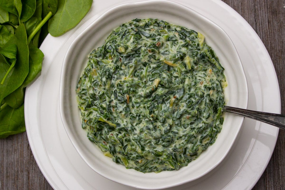 Creamed Spinach in a serving bowl sitting on a plate 2