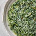 Creamed Spinach in a serving bowl sitting on a plate p4