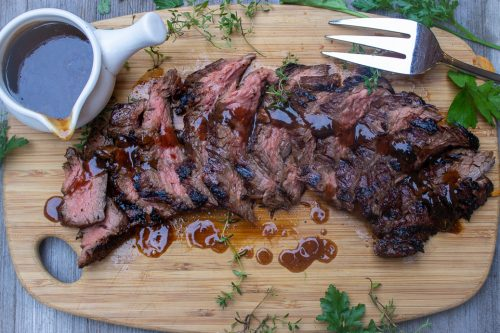 sliced marinated flank steak on cutting board with cup of sauce on side