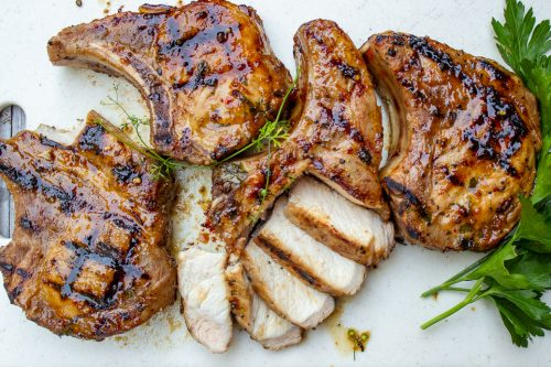 Vietnamese Pork Chops glazed and cooked on cutting board, one chop sliced to show meat