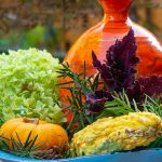 arrangement of fall gourds, leaves, greenery, hydrangeas and an orange vase in a wide mouth bowl