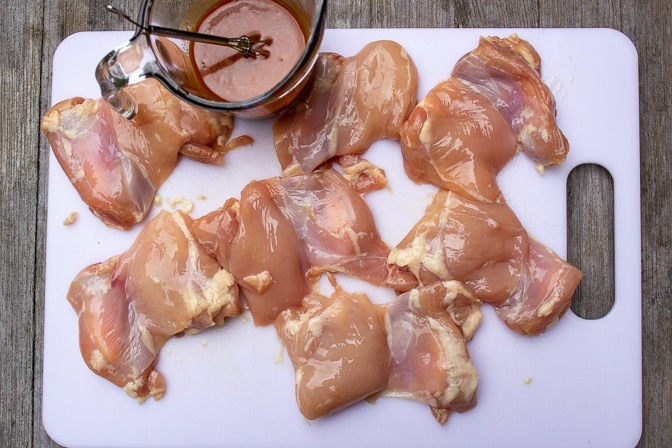 raw chicken thighs on cutting board and BBQ marinade in measuring cup