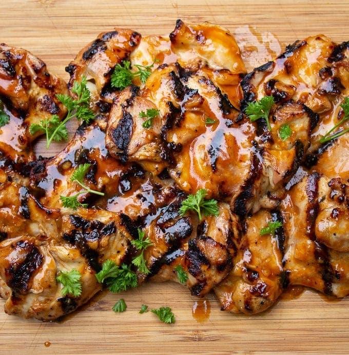 Grilled BBQ boneless Chicken thighs on cutting board