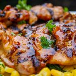 Grilled BBQ Chicken boneless thighs on corn niblets on cutting board p