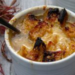 French onion soup in bowl on gray wood board