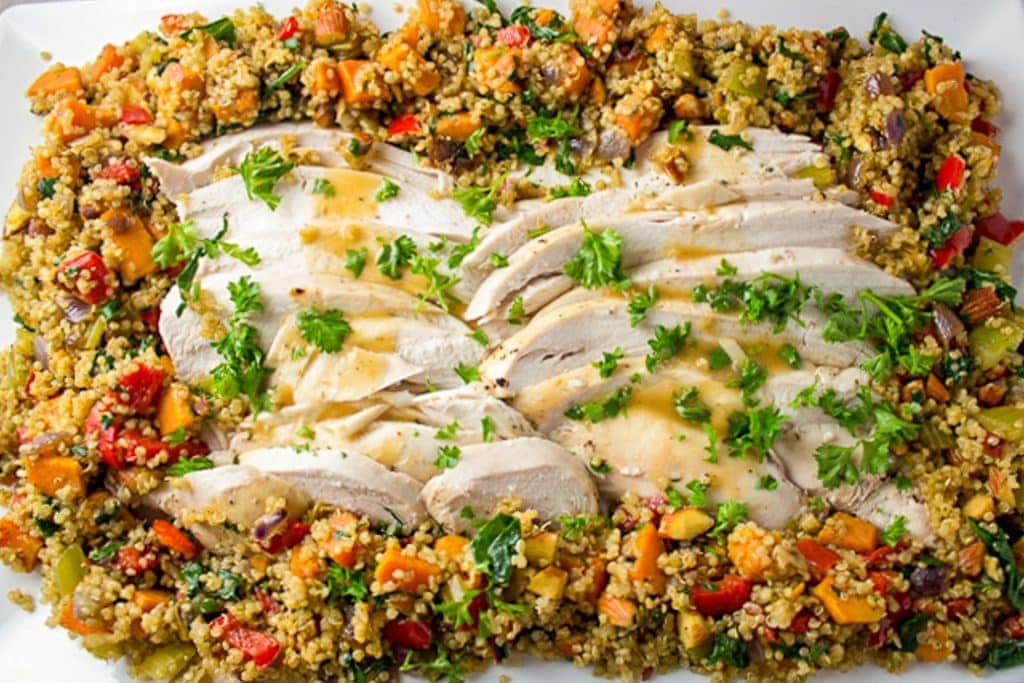 sliced turkey surrounded by quinoa veggie stuffing on a platter