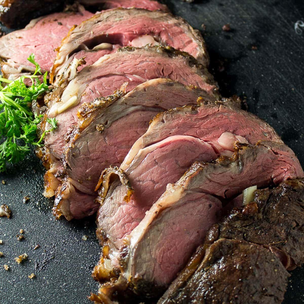 medium rare classic prime rib reverse sear sliced on cutting board f
