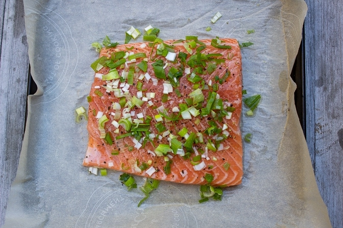 whole piece of salmon with herbs on parchment covered pan