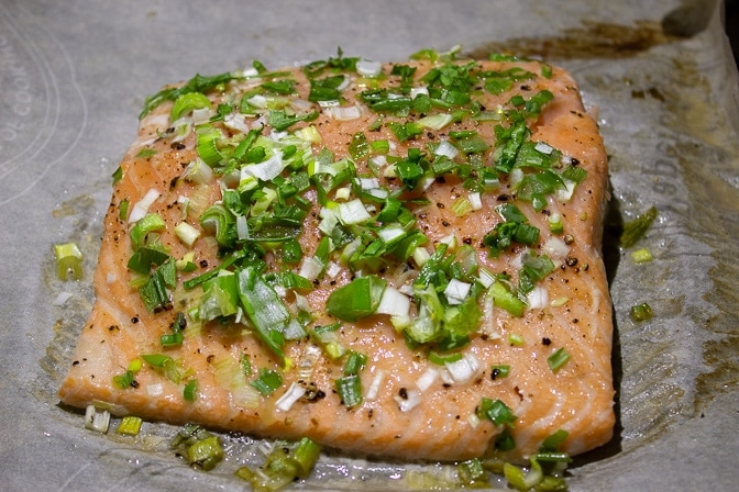 whole piece of Roasted Salmon With Gremolata cut up on pan.