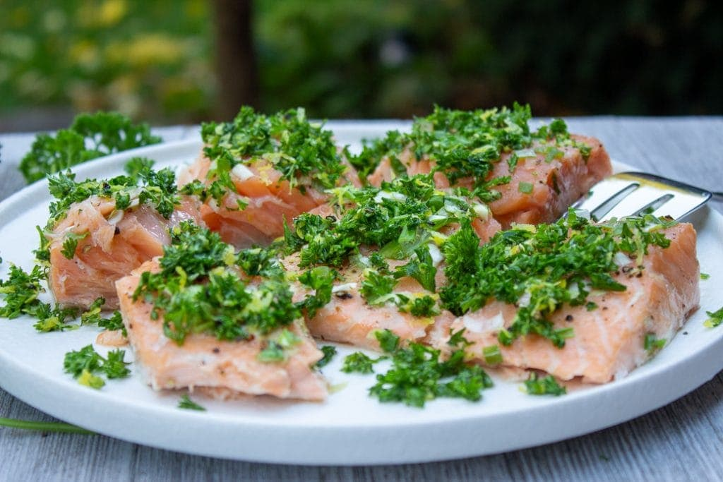 Slow Roasted Salmon With Gremolata cut up on plate. garden in background