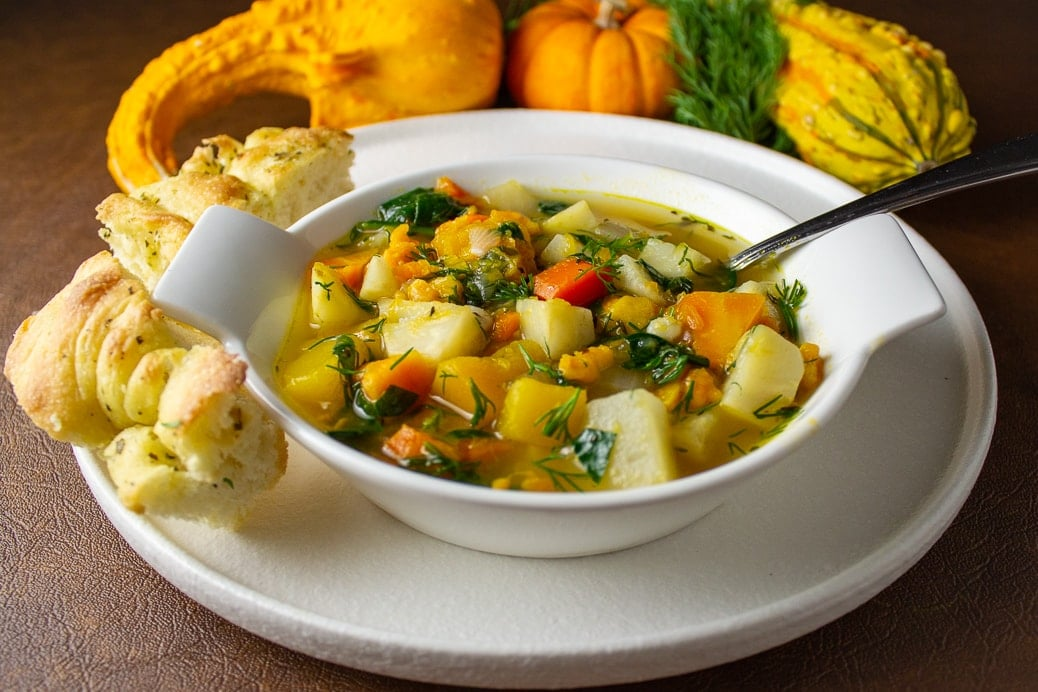 bowl of root vegetable and barley soup with gourds in background. Bowl on plate with bread