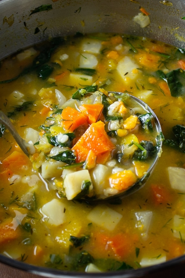 Root Vegetable Soup With Barley in pot with ladle scooping soup