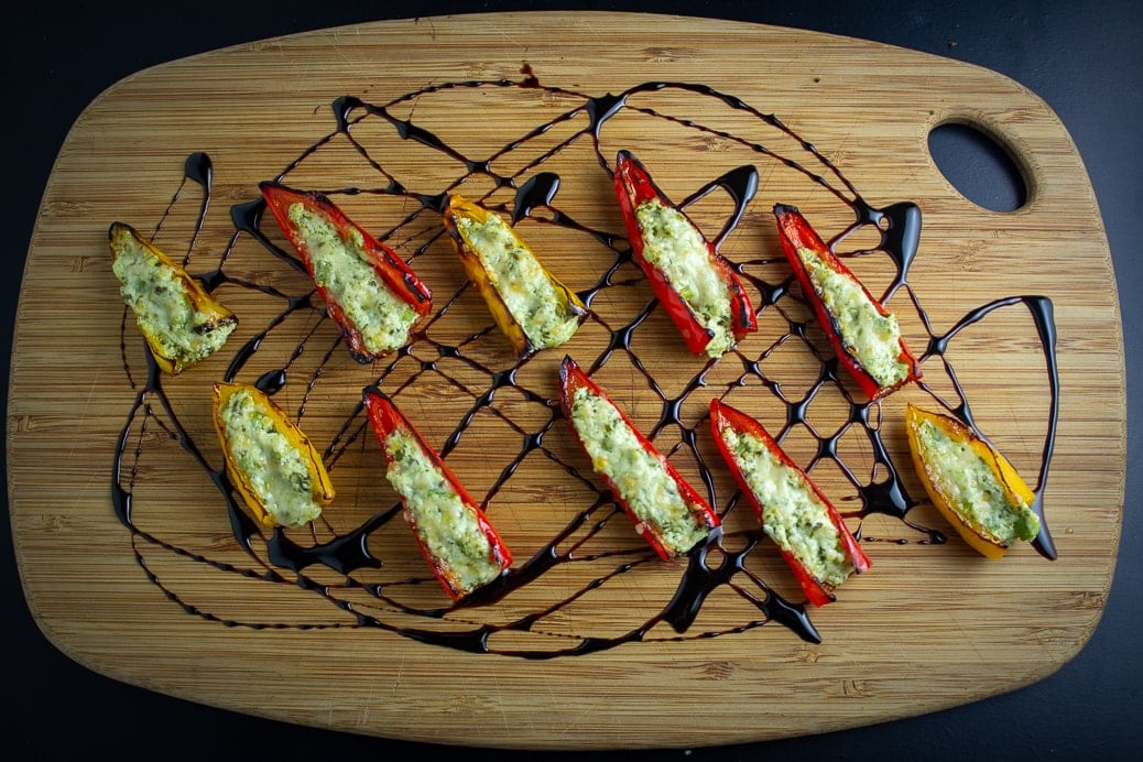 Stuffed Mini Peppers With Goat Cheese on cutting board drizzled with balsamic reduction