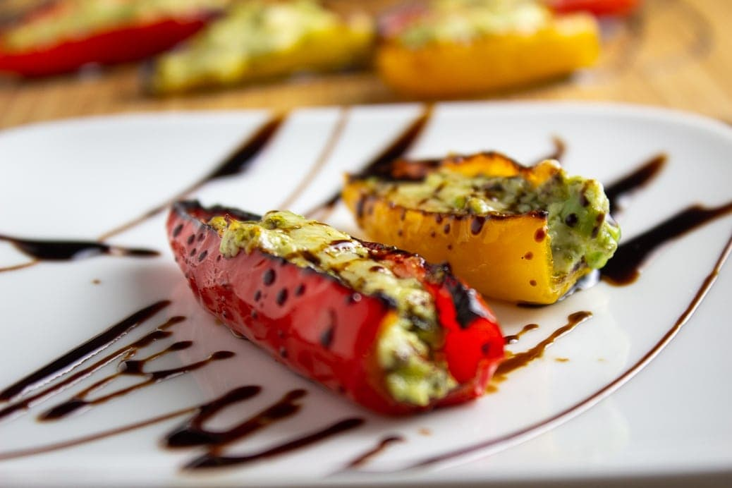 close up of 2 stuffed mini peppers on plate drizzled with balsamic