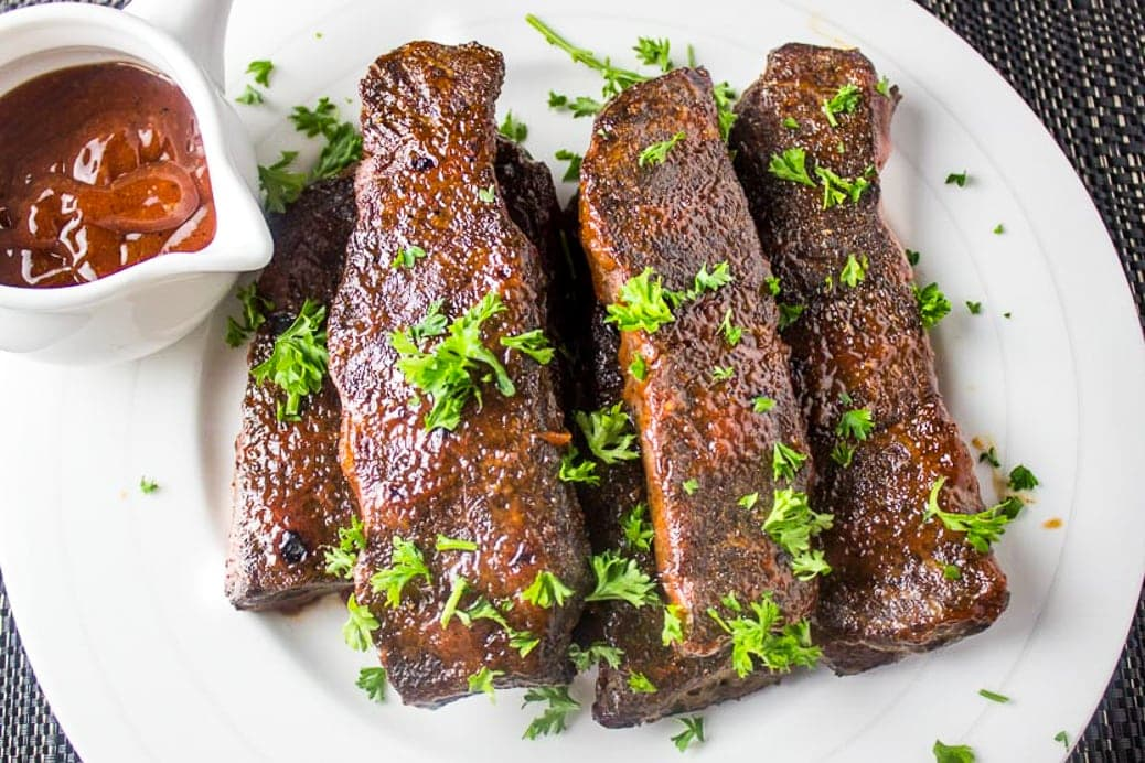 sous vide boneless beef ribs piled on a plate with BBQ sauce on side