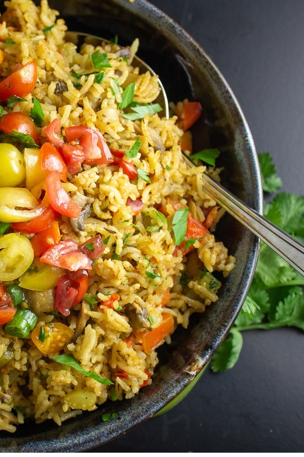 instant pot veggie rice in a bowl with tomato salad on top p