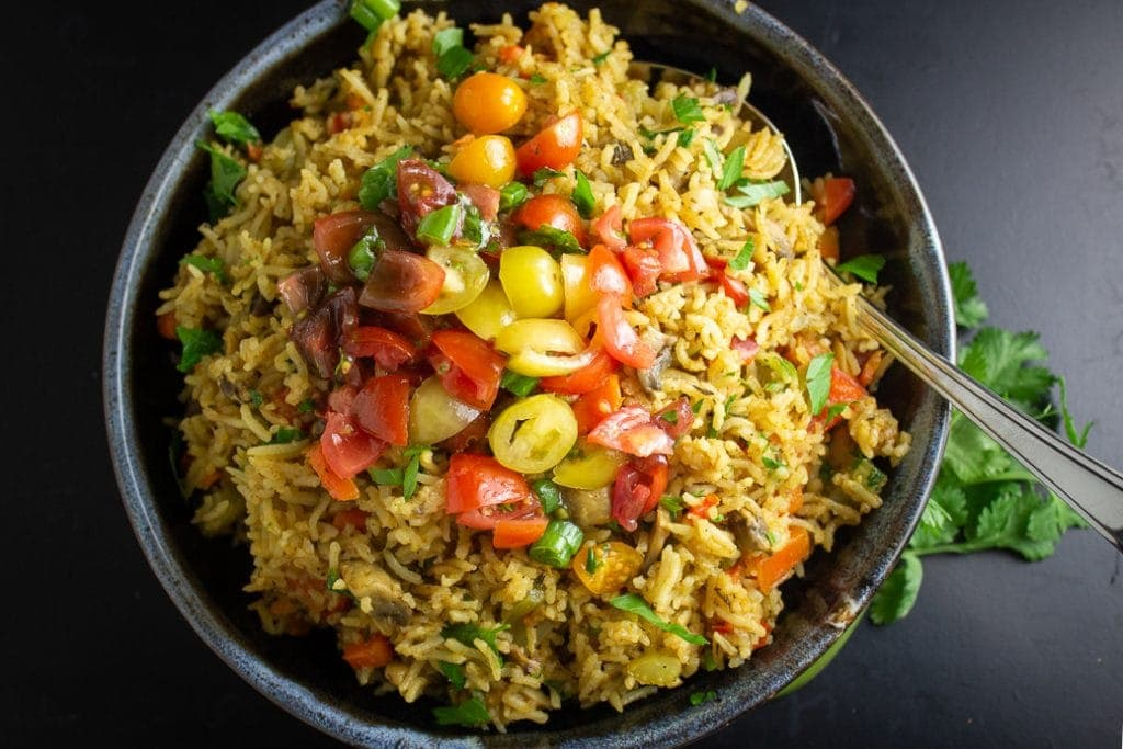 Vegetable Rice in bowl topped with fresh tomato salad
