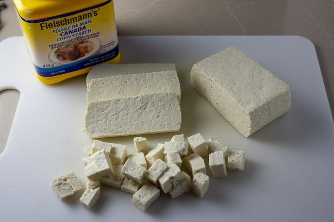 block of tofu partially cut on cutting board into cubes with cornstarch on the edge