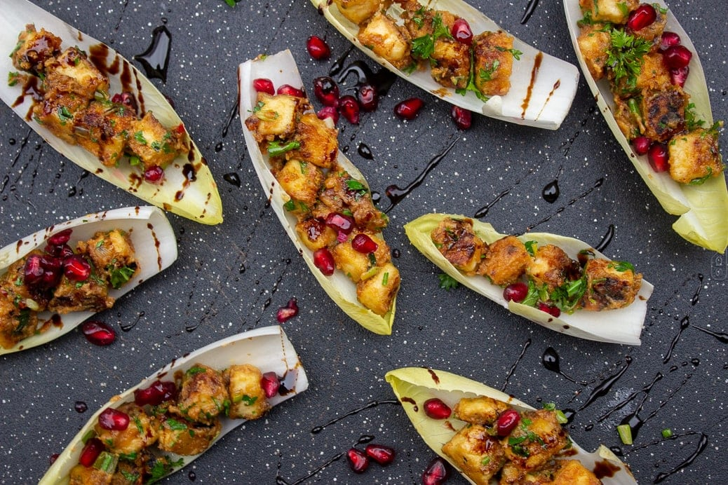 Tofu With Peanut Sauce in endive cups on black cutting board garnished with pomegranate seeds and parsley