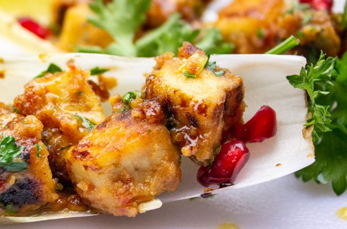 Tofu With Peanut Sauce close up garnished with pomegranate seeds and parsley in endive cup F
