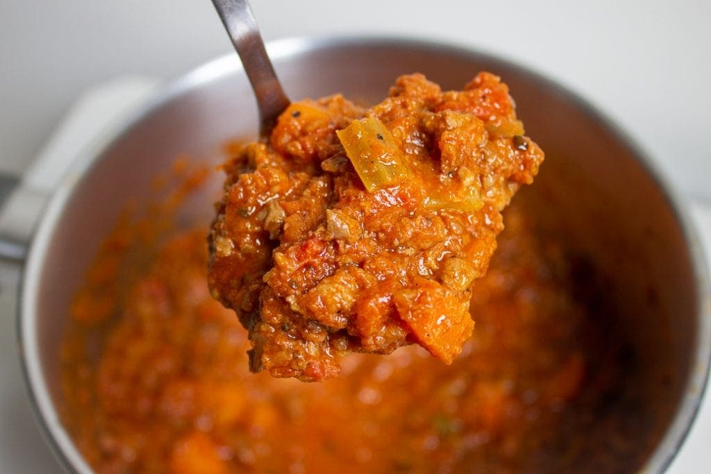 scoop of vegetarian bolognese over a pot
