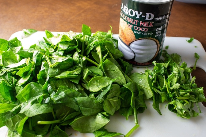 chopped fresh spinach and coconut milk on cutting board