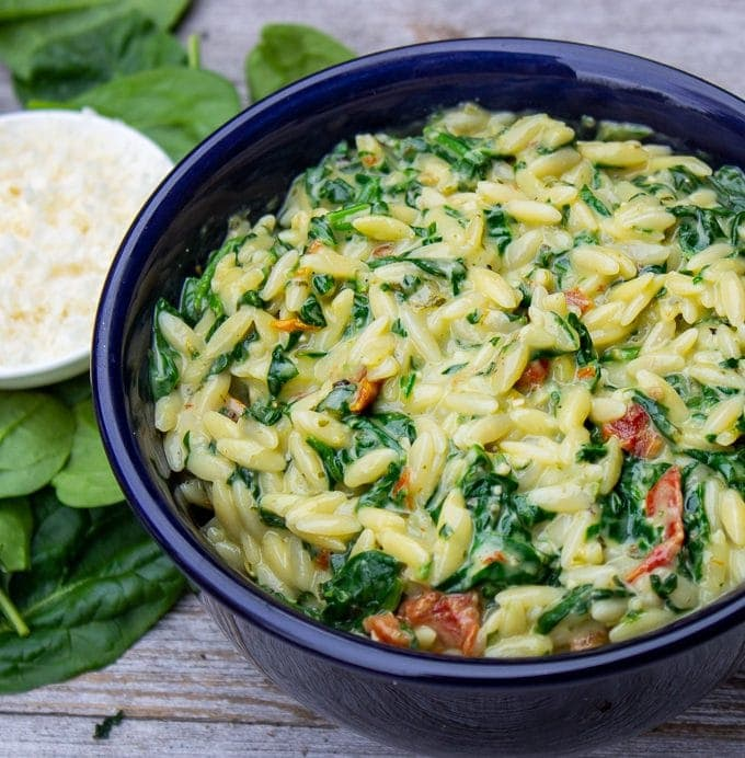 Parmesan Orzo with spinach in ceramic bowl on wood board with small bowl of Parmesan on side 1