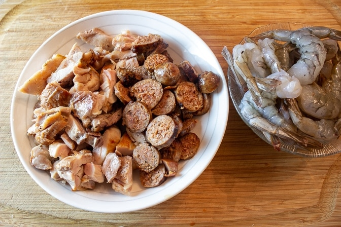 cooked Chorizo sausage and chicken in bowl. raw shrimp in separate bowl