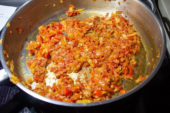 onions, seasonings and tomatoes in pan