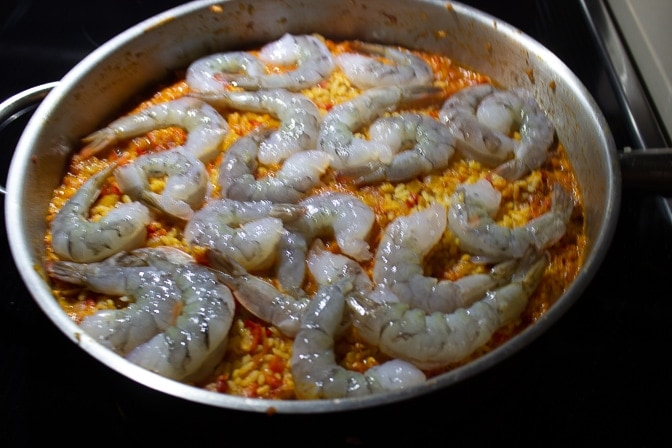 paella in large pan with shrimp laying on top just one side cooked